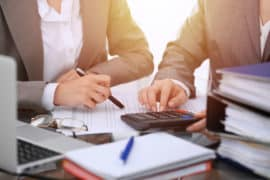 Two Female Accountants Counting On Calculator Income For Tax Form Completion Hands Close Up. Business And Audit Concept
